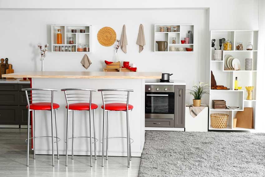 Cucina rossa e bianca con penisola e top in legno, sgabelli rossi.