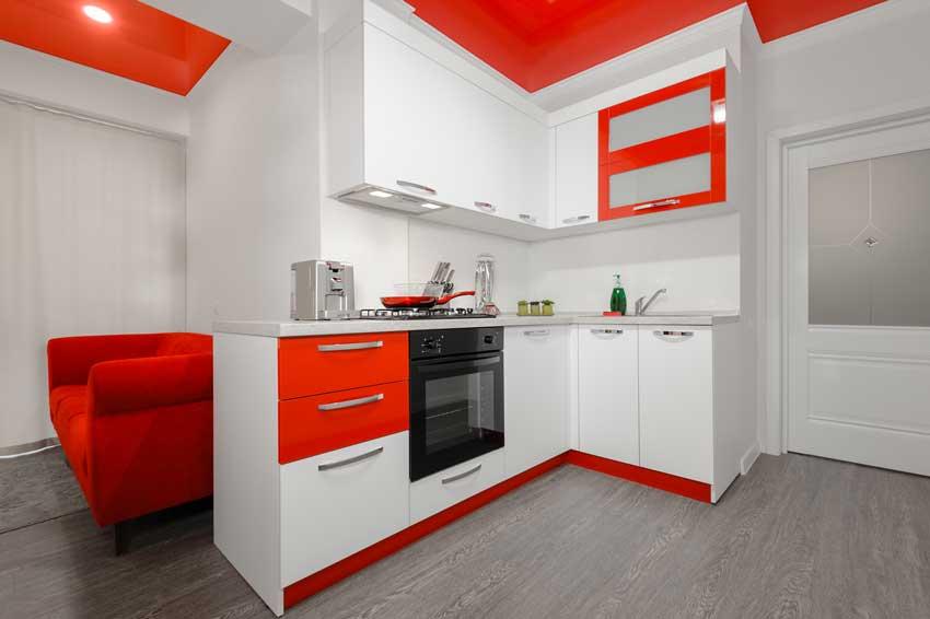 Piccola cucina ad angolo bianca con cassetti e zoccolatura rossi, pareti bianche e soffitto rosso.