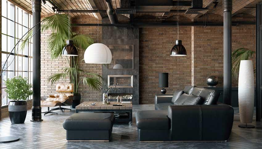 Grande loft con mattoni rossi a vista, stile di arredamento industrial, divano in pelle nera con pouf.