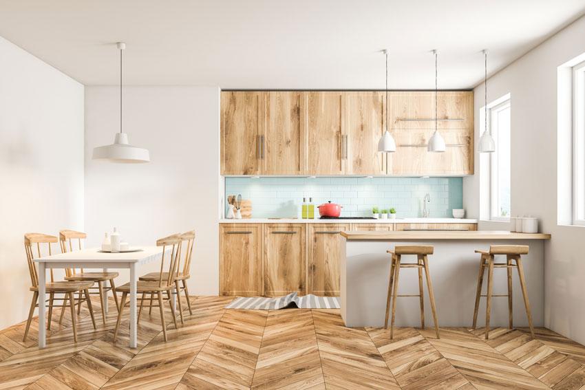 Ambiente open space stile nordico con cucina e sala pranzo in legno.