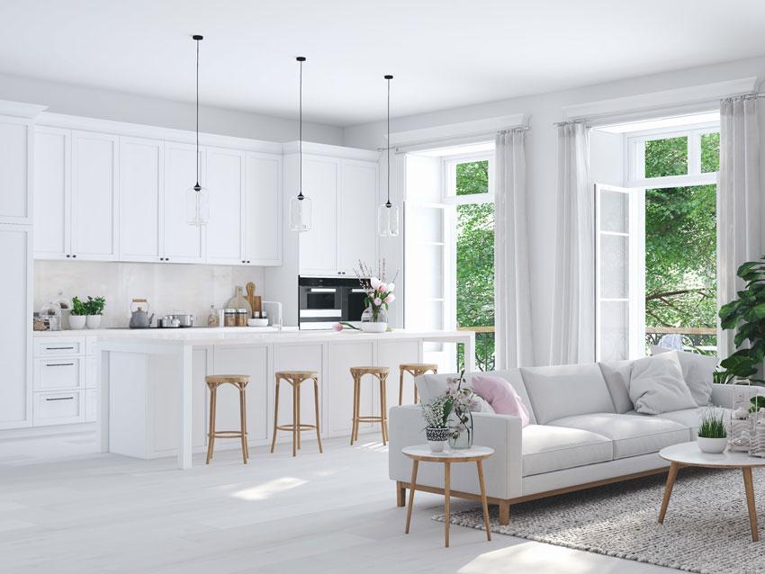Bellissima cucina bianca aperta sul soggiorno con delicati tocchi di colori.