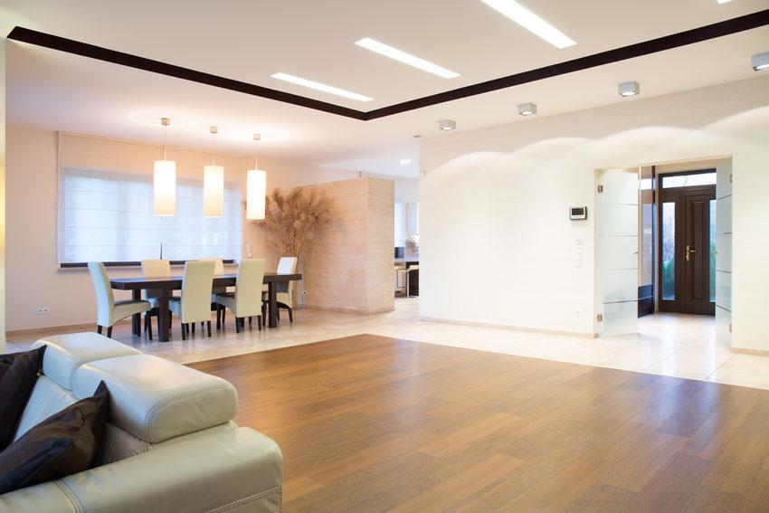 Arredamento loft open space stile minimal con parquet centrale.