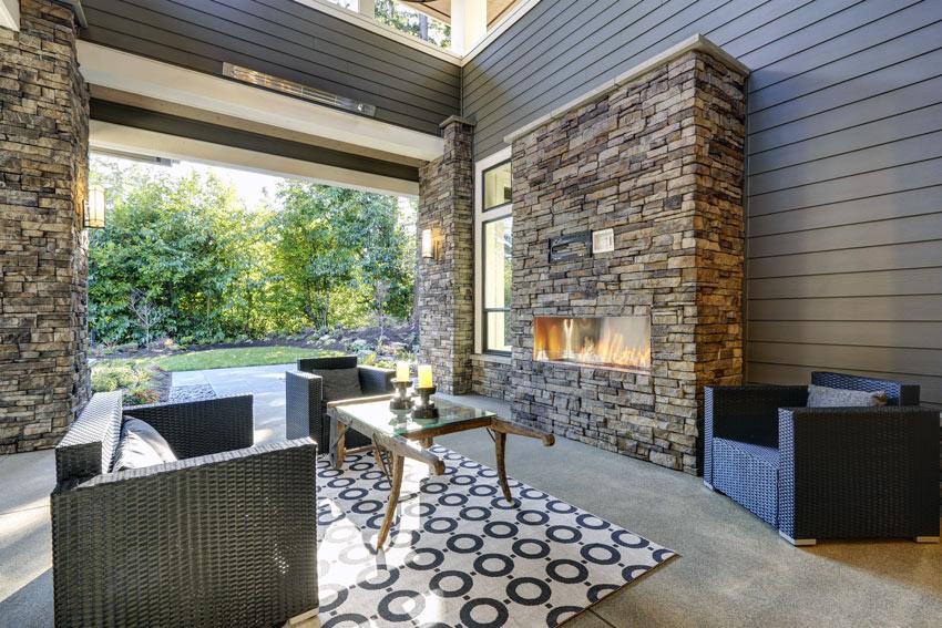 camino moderno con parete rivestita in pietra in questo soggiorno.