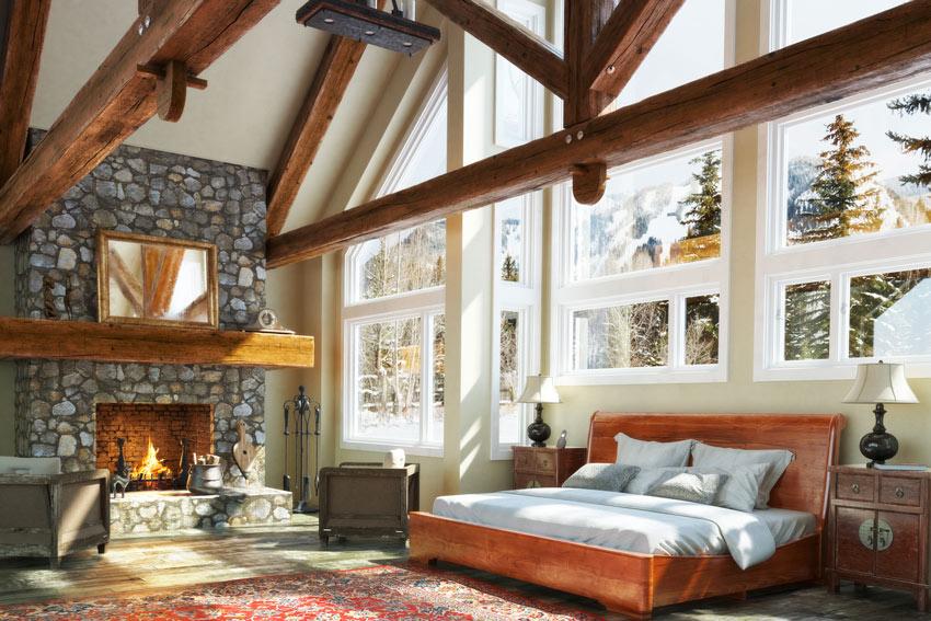 Camera da letto con camino e parete rivestita in pietra naturale.