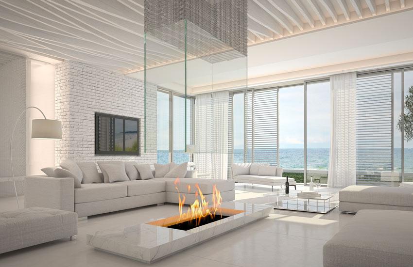 Splendido salotto moderno bianco e camino con cappa in vetro trasparente.