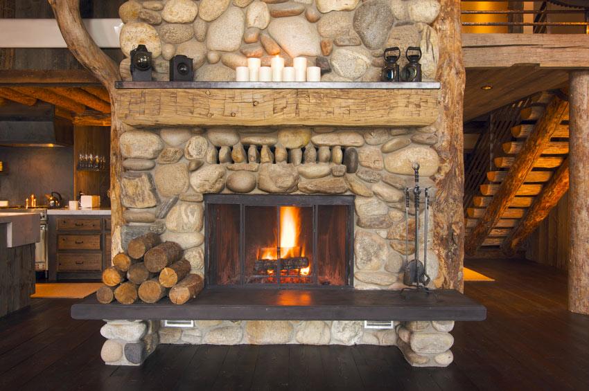 Bel caminetto rivestito di pietre e sassi, travi in legno.