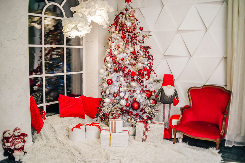 Soggiorno con albero di Natale bianco e decorazioni rosse.