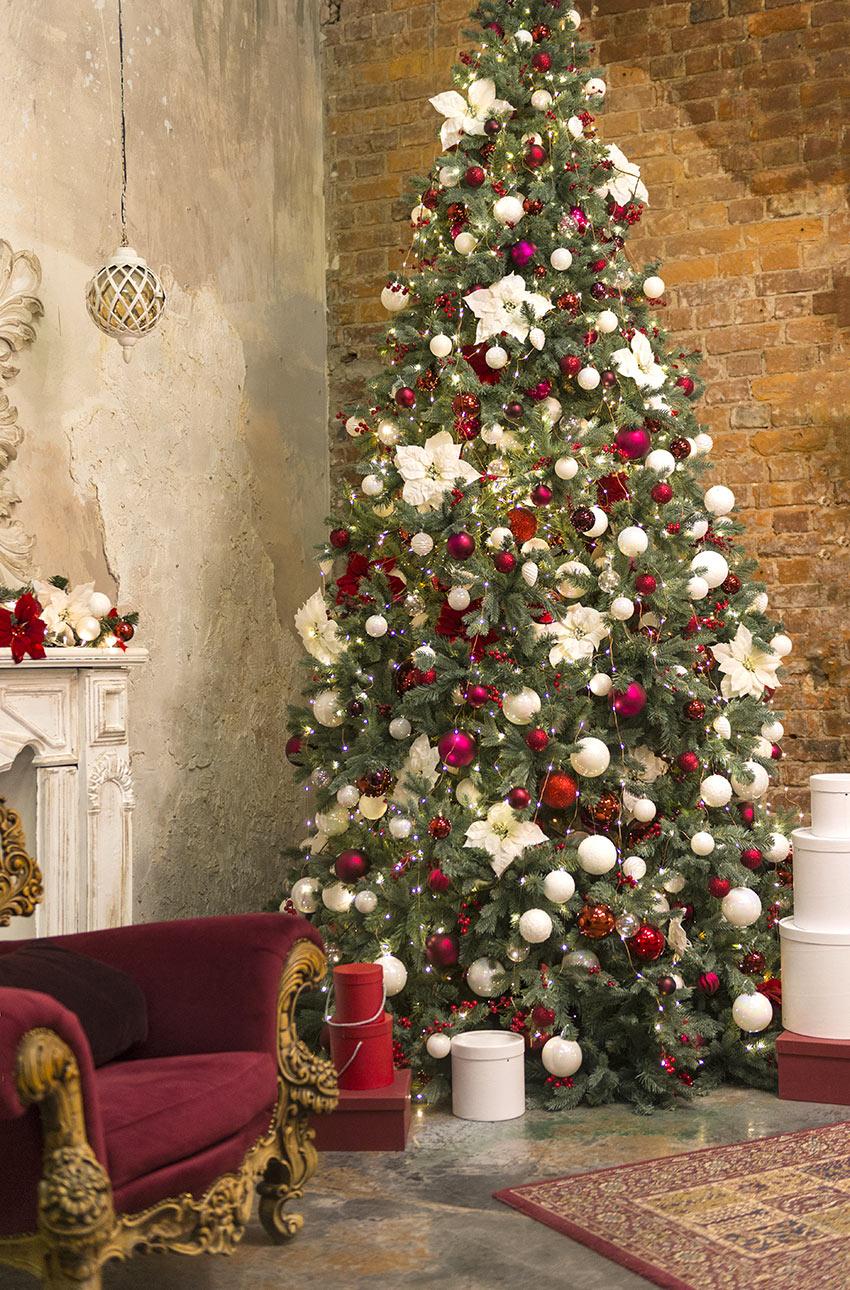 Albero di Natale verde addobbato in bianco e rosso.