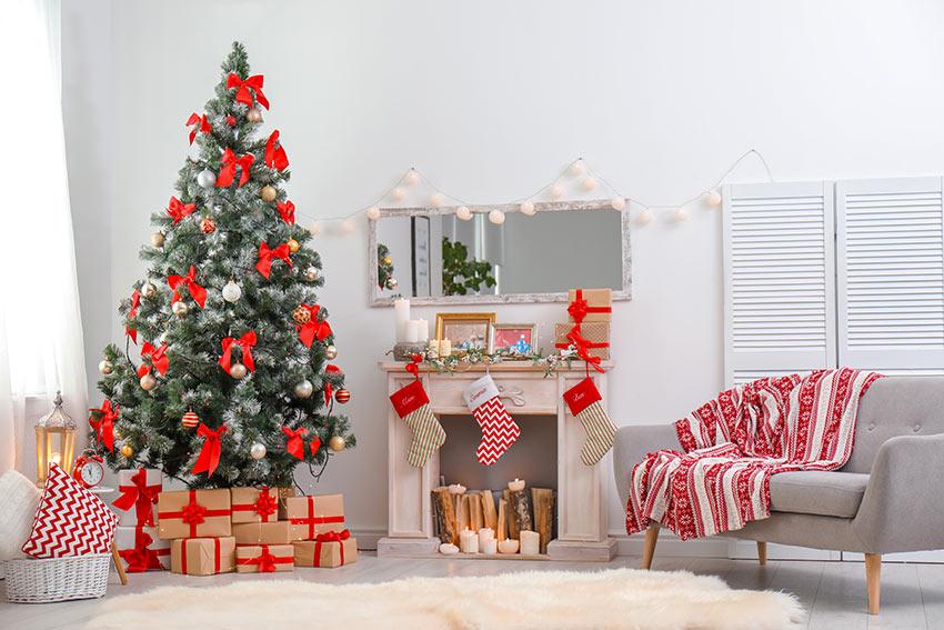 Salotto con albero di Natale addobbato con fiocchetti rossi e palline bianche.