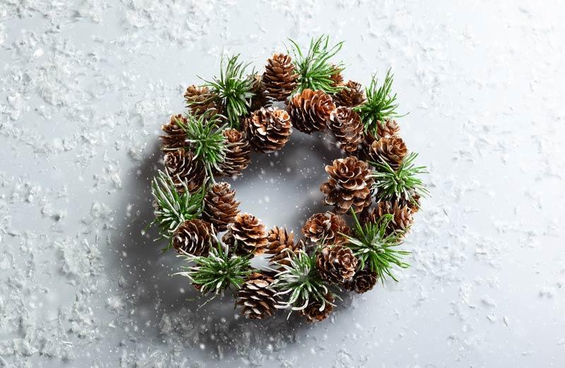 Ghirlanda decorativa natalizia fai da te con pigne e rami di pino.