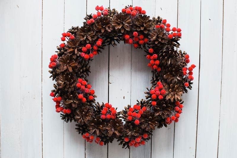 Ghirlanda natalizia fai da te realizzata con pigne e bacche rosse.
