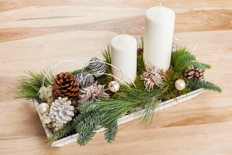 Portacandele natalizio con pigne e rami di pino.