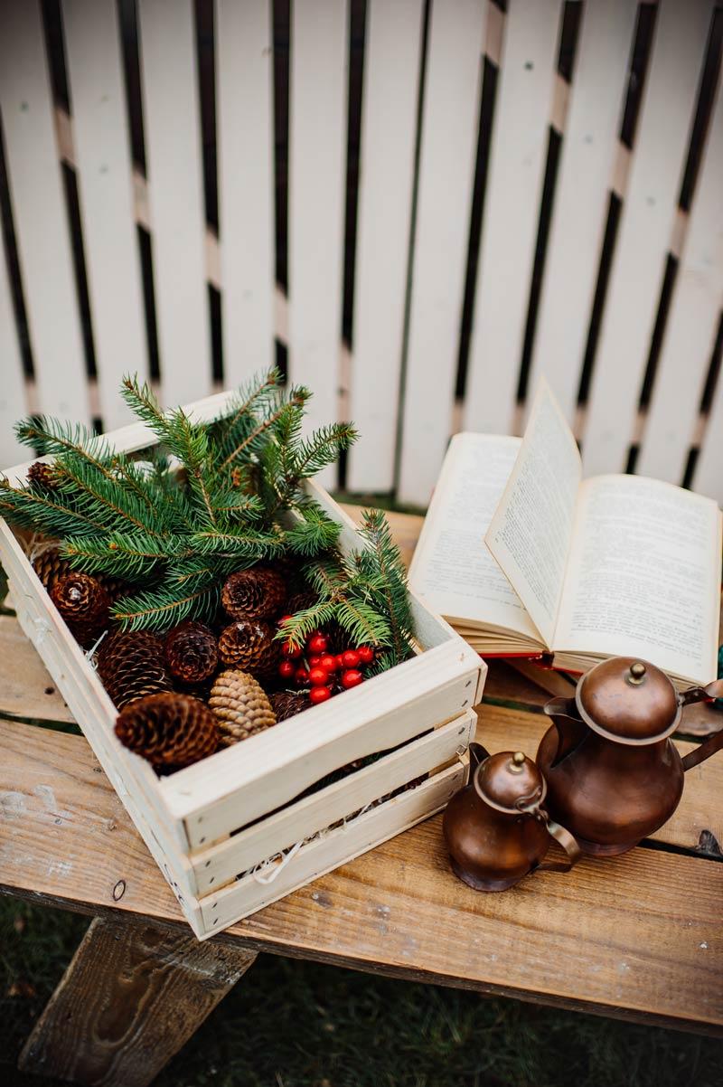 Decori natalizi fai da te con cassette di legno e pigne.