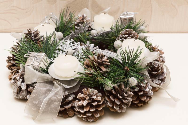 Centrotavola natalizio fai da te realizzato con pigne e rami di pino.
