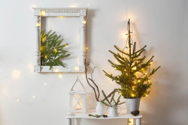 Alberello di Natale illuminato su comodino, bello quadro natalizi sulla parete con rami di pino.
