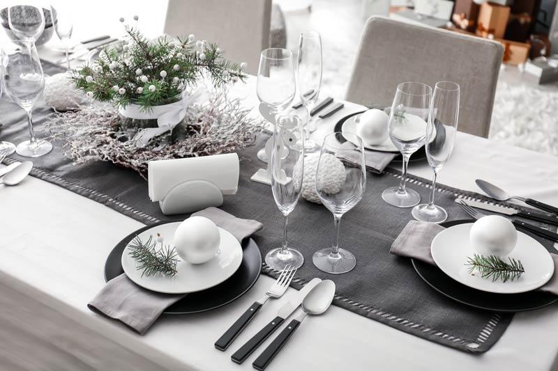Tavola di Natale addobbata in bianco e grigio, piatti decorati con palline di natale e ramo di pino.