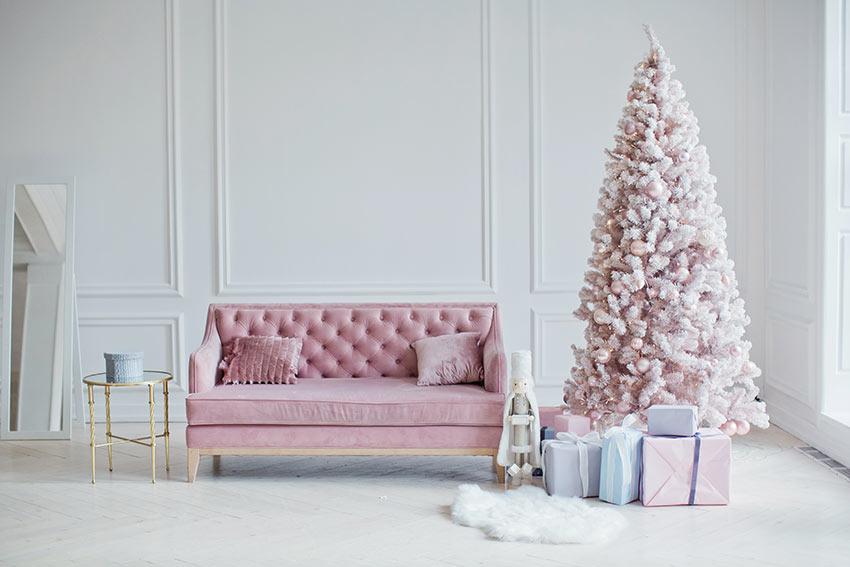 Soggiorno con bel divanetto e albero di Natale rosa chiaro e bianco.