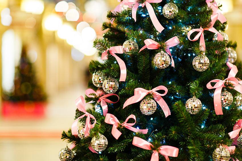 Albero di Natale con fiocchetti rosa e palline dorate.