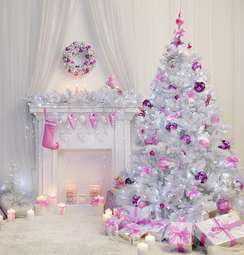 Salotto decorato per le feste di Natale con caminetto e albero bianco con addobbi rosa e viola.