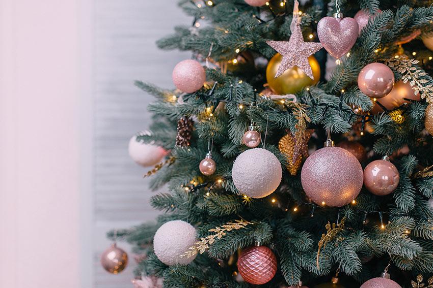Albero di Natale con palline e stelline rosa e bianche.