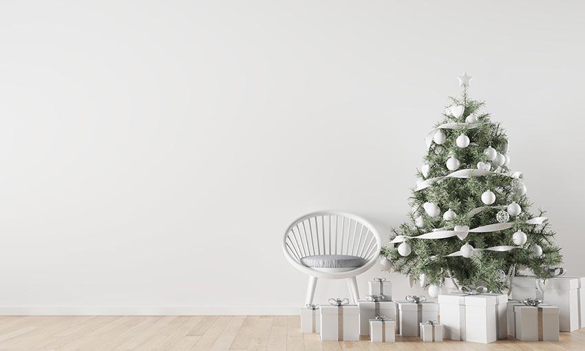 Piccolo albero di Natale decorato in stile shabby chic con festone e palline bianche.