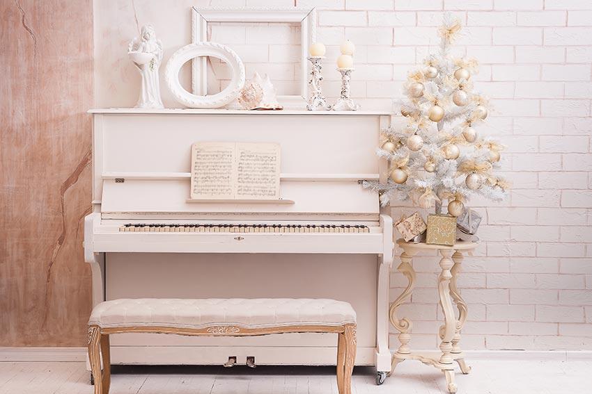Albero bianco vicino ad un piano forte decorato con palline dorate.