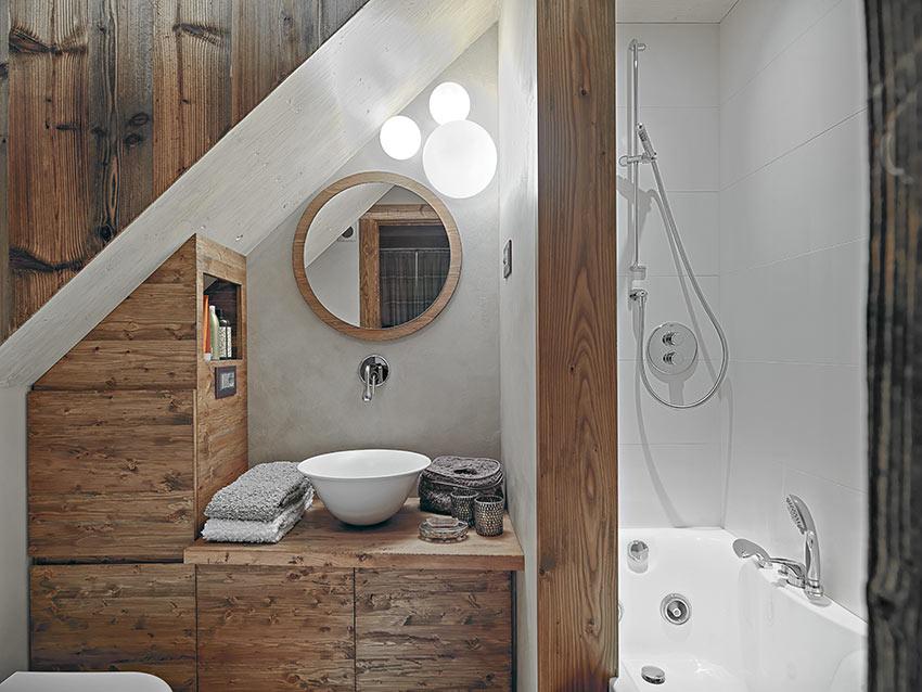 Un piccolo bagno in muratura stile rustico con rivestimento in legno e vasca doccia.