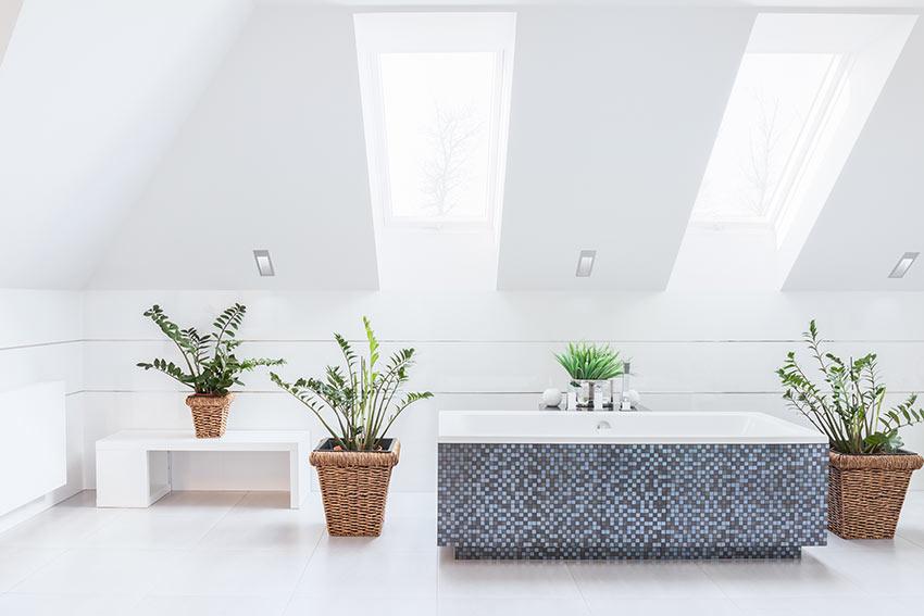 Vasca da bagno in muratura rivestita di piastrelle blu effetto mosaico.