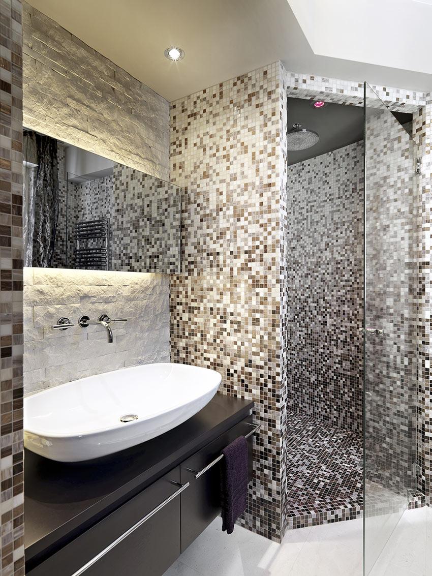 Bellissimo bagno con rivestimento in pietra e doccia realizzata in muratura rivestita con mosaico.