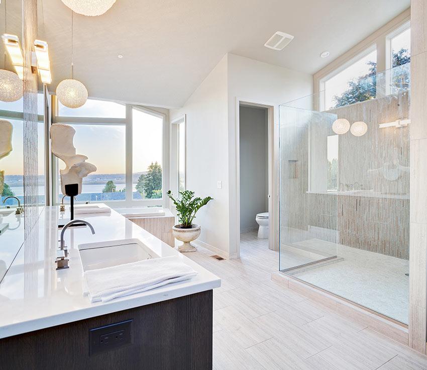 Grande bagno luminoso in muratura con doccia e box in vetro.