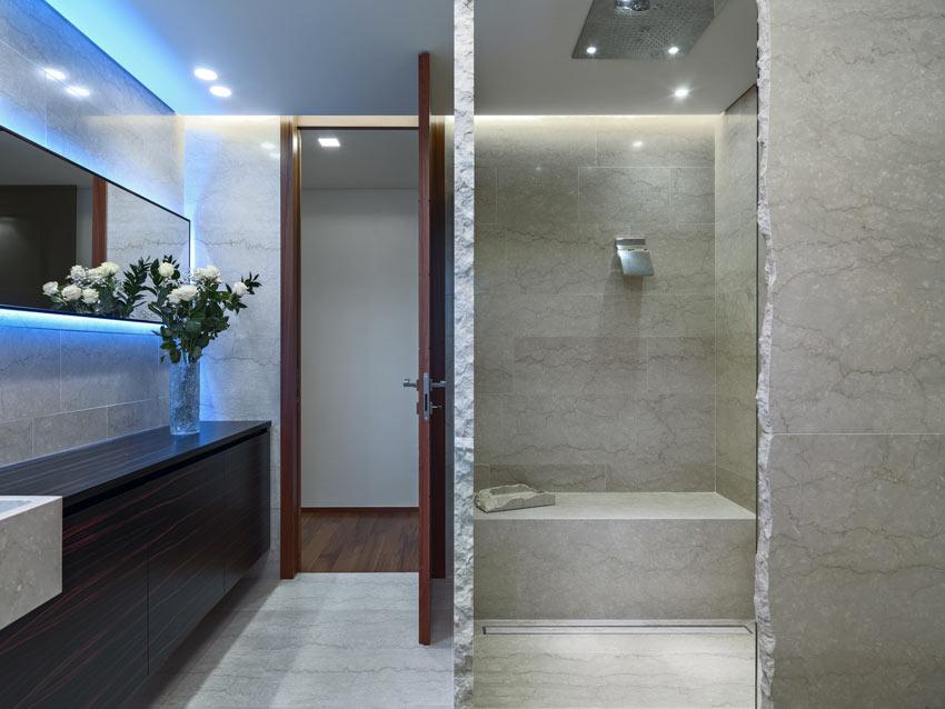 Bel bagno con doccia in muratura con seduta, illuminazione moderna con luci a LED.