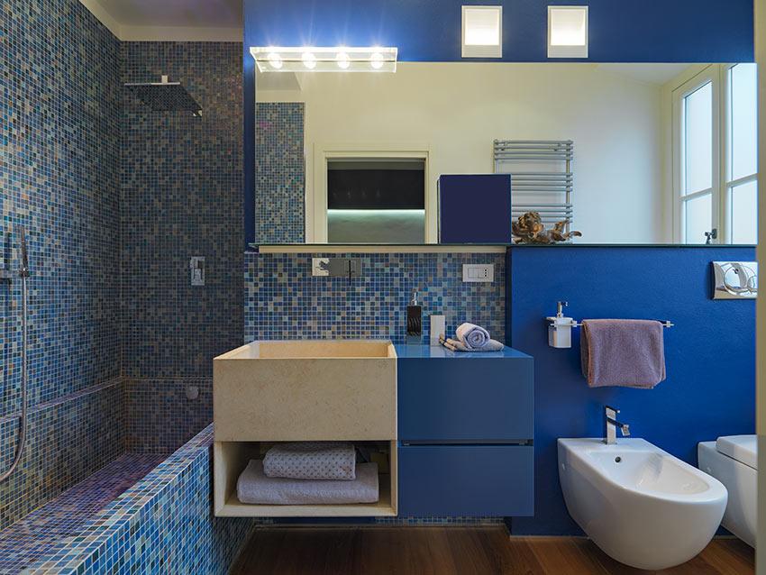 Bagno moderno con rivestimento in piastrelle blu effetto mosaico.