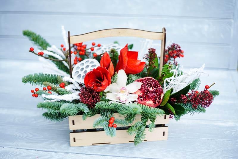 cassette di legno con melograno secco aghi di pino, bacche e fiori, ideale per decorare il Natale.