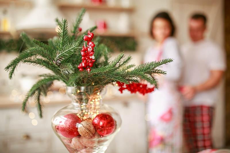 Vaso di vetro con noci, frutto invernale, palline colorate e rametti.