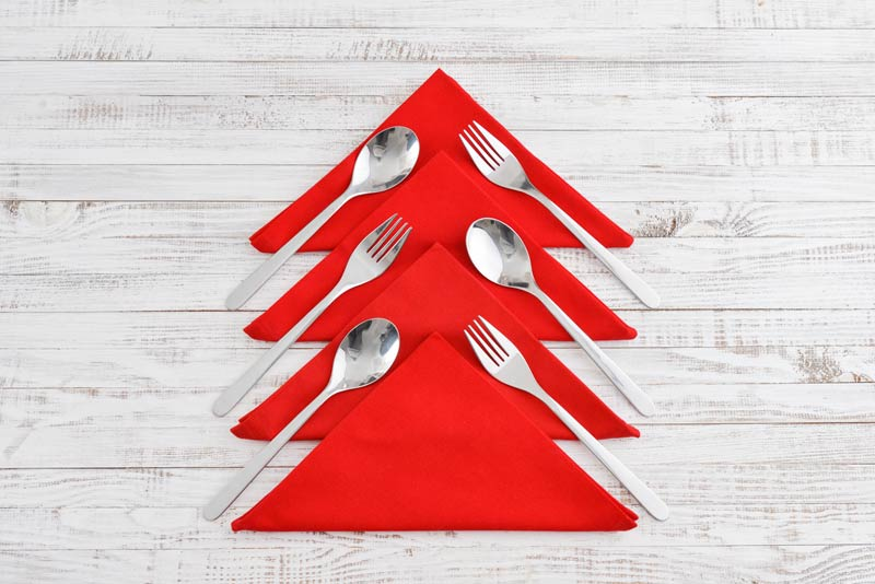 Tovaglioli rossi piegati a forma di albero di Natale per decorare la tavola.