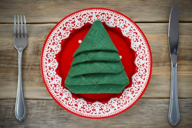 Come piegare un tovagliolo a forma di albero per decorare la tavola a Natale.