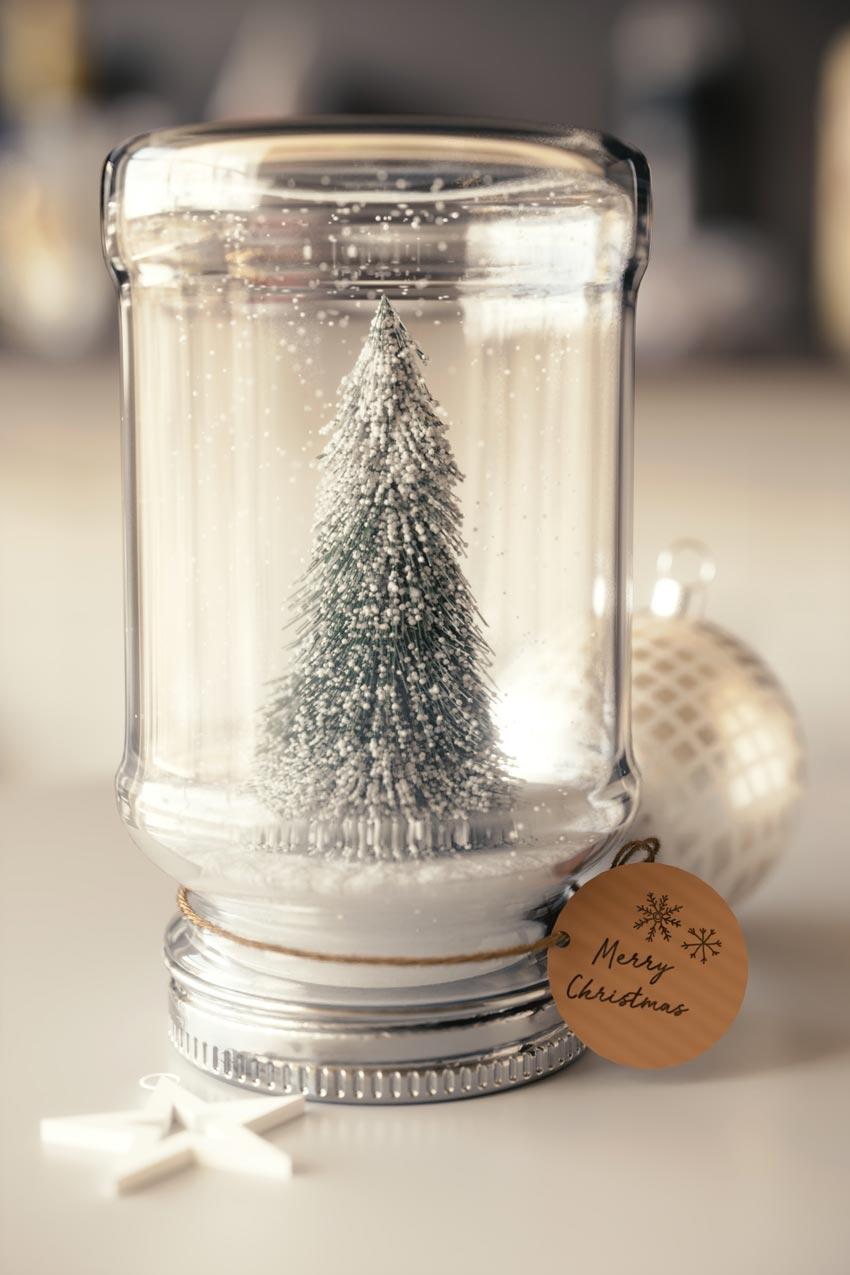 Vasetto di vetro riciclato decorato con un piccolo albero di Natale innevato.