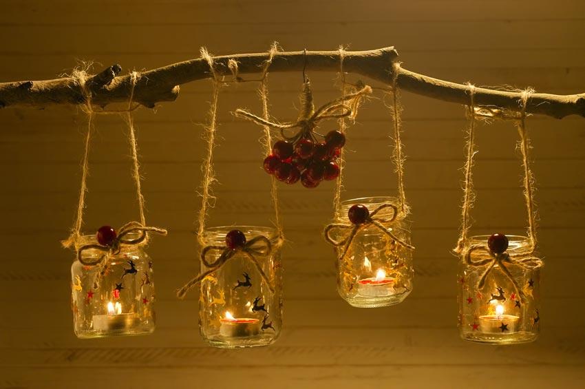 Ramo di legno con barattoli natalizi sospesi con corda.