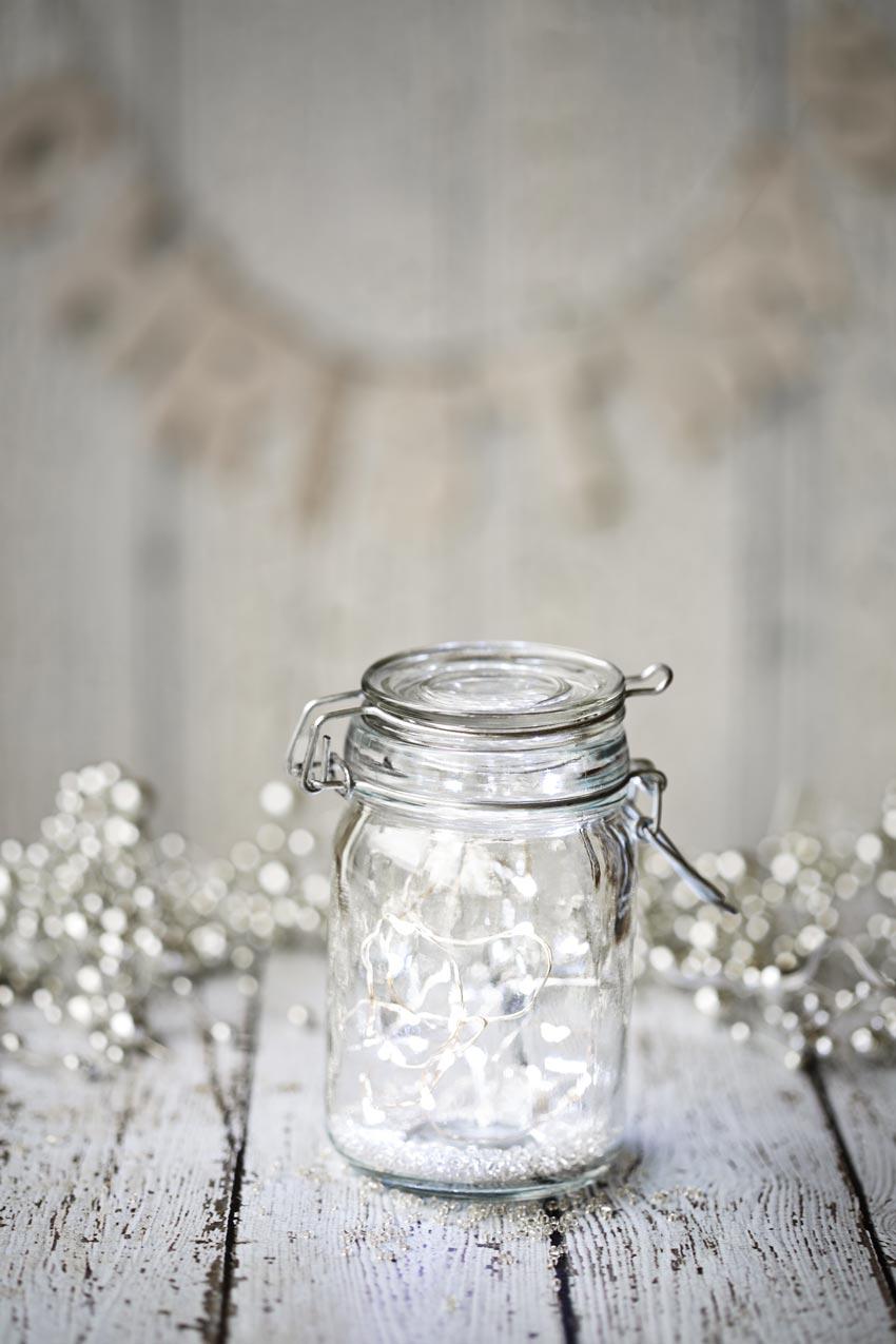 Barattolo di vetro decorato per Natale con lucette bianche.