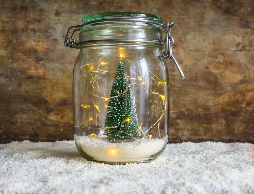 Piccolo vaso di vetro con lucette e alberello di Natale all'interno.