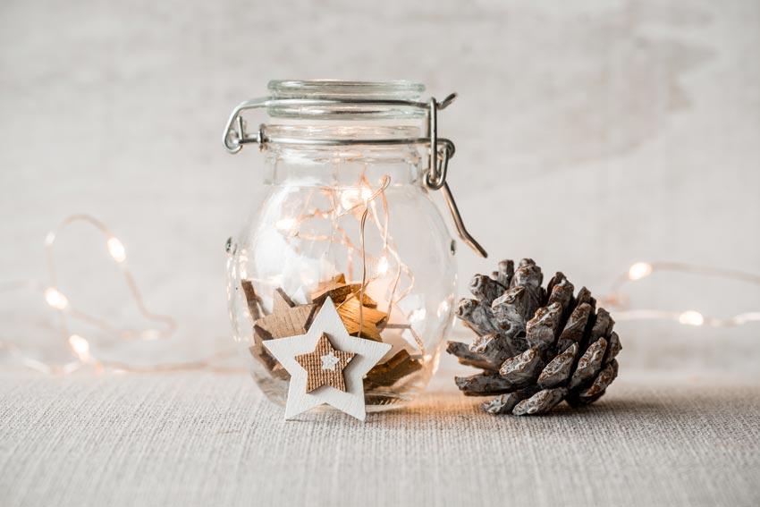 Vaso di vetro natalizio decorato con stelle, lucette e pigna.