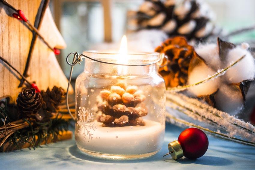 Vasetto di vetro decorato con una pigna candele.