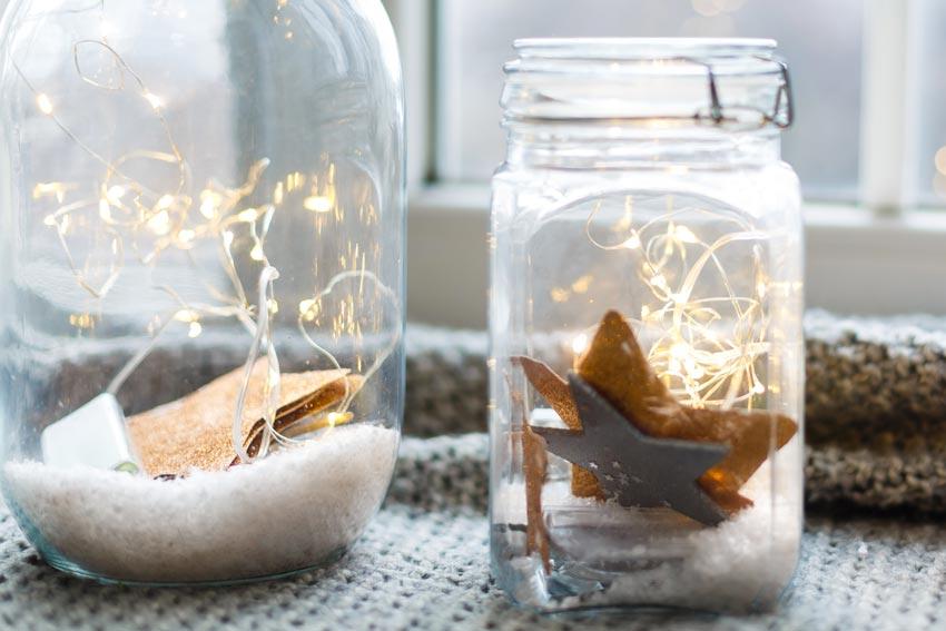 vasetto di vetro natalizio decorato con finta neve, stelline e lucette.