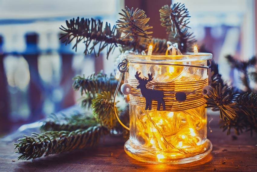 Vasetto di vetro decorato con lucette e renne natalizie.