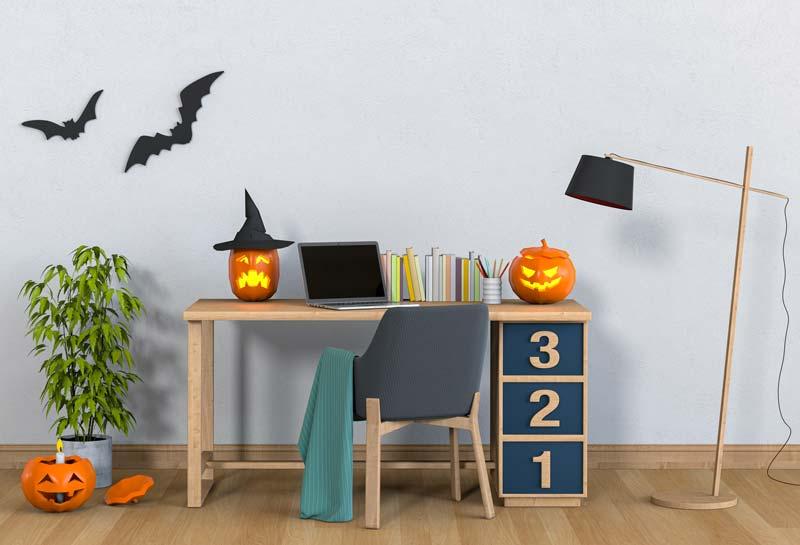 Scrivania decorata con zucche e pipistrelli per la festa di Halloween.