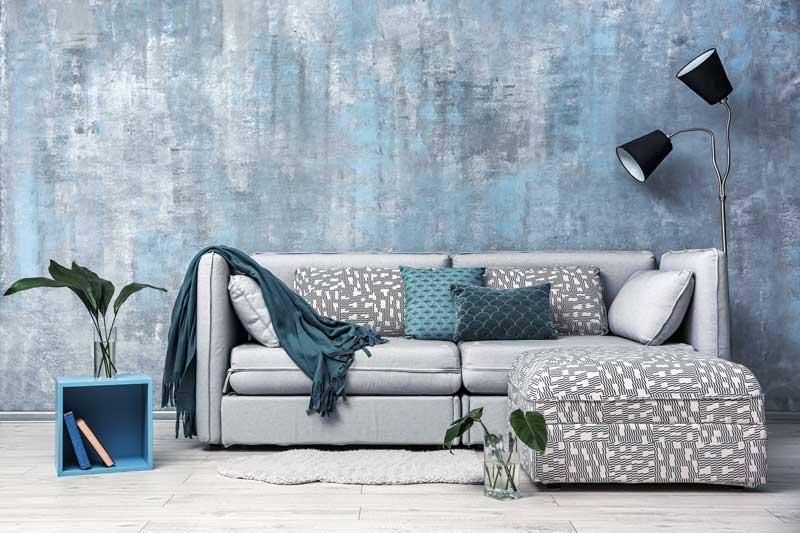 Divano grigio con cuscini fantasiosi, parete moderna con pittura particolare.