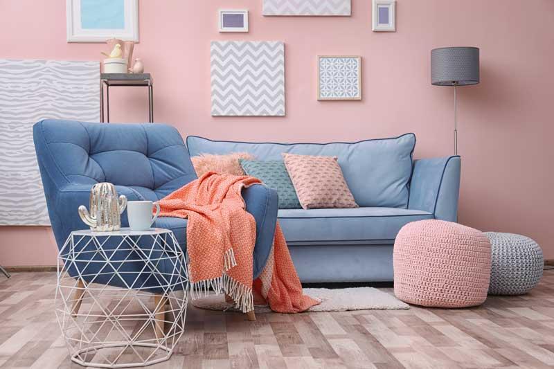 Soggiorno bellissimo stile moderno con divano e poltrona celesti, parete rosa.