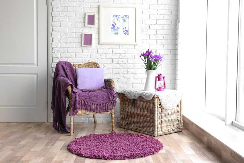 Un angolo shabby chic con parete a vista bianchi, sedia e contenitore in vimini.