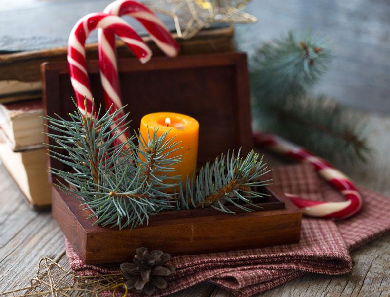 Cofanetto decorativo natalizio con candela e rami di pino.