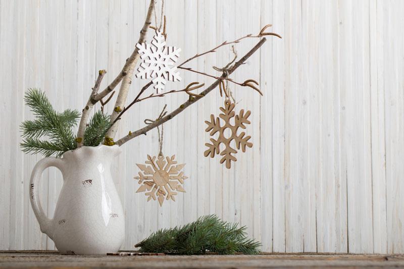 Vaso bianco natalizio con rametti di legno e rami di pino.